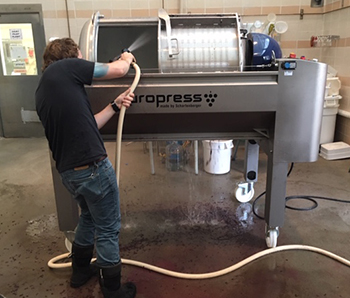 Food Science graduate student Jared Johnson cleaning a winery press after processing a batch of Pinot noir wine