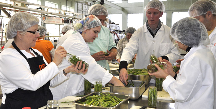 Fruit and vegetable processing short course participants packing asparagus in glass jars. Photo credit: Tiffany Woods