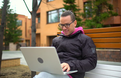 Male student studying outdoors on laptop computer
